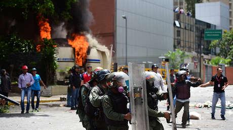 Los empleados de la estatal Venezolana de Televisión están de pie frente a un puesto de policía en llamas, mientras los agentes antidisturbios contienen a los manifestantes de la oposición durante una protesta contra el gobierno en Caracas, el 20 de julio de 2017.