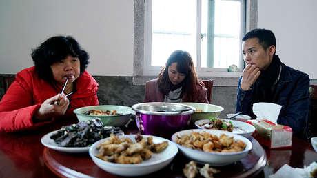 La bloguera Zhao Yuqing (centro) revisa su teléfono móvil durante una comida con la familia de Wang Quanming, en Anxi (Fujian, China).