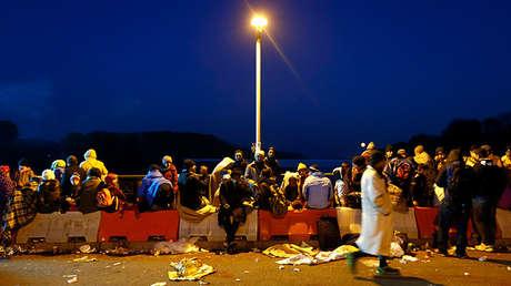 Inmigrantes esperan en un puente en la frontera entre Austria y Alemania cerca de Passau (Alemania), el 27 de octubre de 2015.