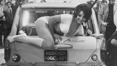 La actriz Julie Desmond sale del maletero de un coche soviético Moskvich 427