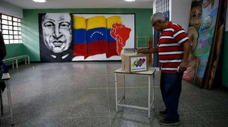 Un hombre deposita su voto cerca de un cuadro del expresidente de Venezuela, Hugo Chávez, durante una elección legislativa, en Caracas el 6 de diciembre de 2015.