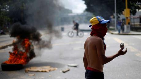 Un manifestante bloquea una calle durante una huelga convocada para protestar contra el gobierno del presidente venezolano, Nicolás Maduro, en Caracas, Venezuela. 27 de julio de 2017.
