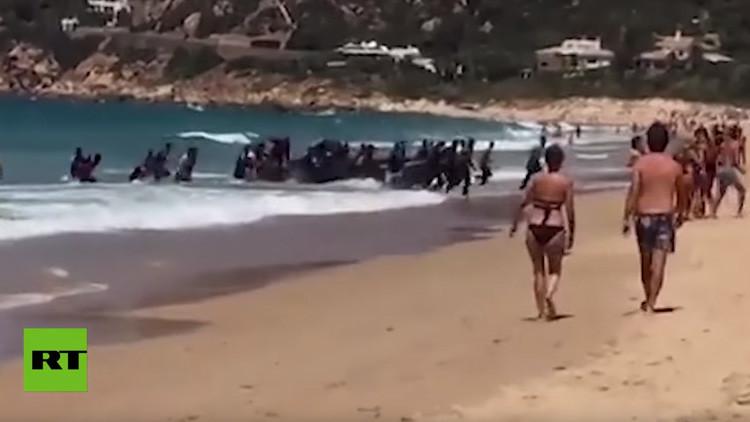 VIDEO: Una patera llena de inmigrantes llega a una playa de España ante el asombro de los bañistas