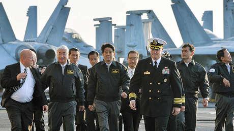 El primer ministro de Japón, Shinzo Abe, el vice primer ministro de Gobierno y ministro de Finanzas, Taro Aso y el entonces ministro de Defensa de Japón, Gen Nakatani, visitan el portaviones USS Ronald Reagan en la bahía de Sagami (Japón). La foto fue difundida el 18 de octubre de 2015.