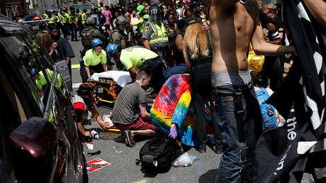 Rescatistas atienden a los heridos después de que un coche embistiera a manifestantes en Charlottesville, EE.UU.