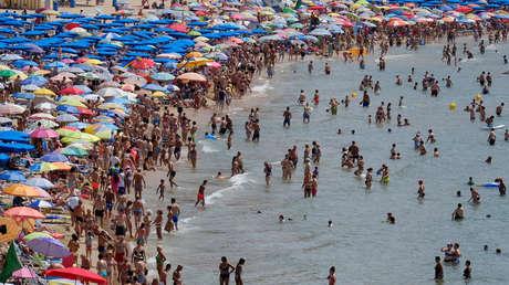 Numerosos turistas disfrutan de las vacaciones vacaciones en la playa de Benidorm, en el sureste de España