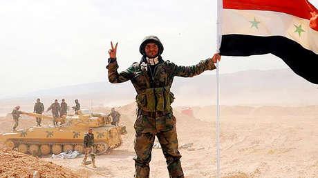Soldados sirios de unidades que desbloquearon la 13ª brigada mecanizada hizan bandera nacional en el territorio de su base.