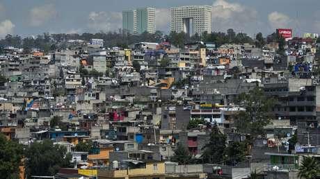 Viviendas humildes de un barranco en Ciudad de México frente a un edificio de lujo