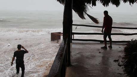 Un hombre observa cómo la marea aleja una mesa de su restaurante antes de la llegada del huracán María a Punta Cana, República Dominicana, el 20 de septiembre de 2017.
