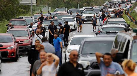 Gente atrapada en un congestionamiento vial en una carretera bloqueada por un río en Yauco, Puerto Rico, tras el paso del huracán Maria, el 21 de septiembre de 2017.