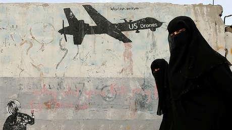 Varias mujeres pasan ante un grafiti que denuncia los ataques con drones de EE.UU. en Yemen, el 6 de febrero de 2017