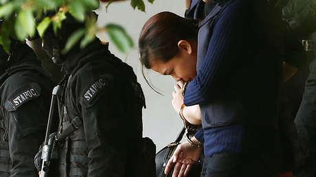 La indonesia Siti Aisyah, acusada de asesinar a Kim Jong-nam, abandona escoltada por la Policía un tribunal de Sepang, Malasia, 13 de abril de 2017.