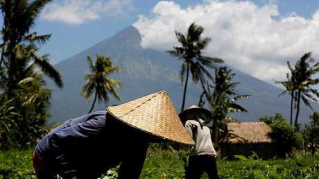 El volcán Agung tras agricultores indonesios, en la isla de Bali, 29 de septiembre del 2017.