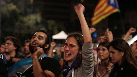 Reacciones de la gente mientras escucha el discurso del presidente catalán, Carles Puigdemont, en la Plaza Catalunya, tras concluir la jornada