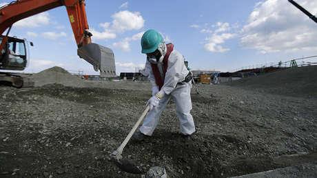 Un trabajador vestido con un traje protector y una máscara nivela la tierra en la planta nuclear de Fukushima I en Japón, el 10 de febrero de 2016.