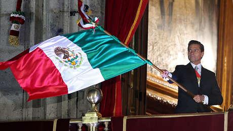 El presidente Enrique Peña Nieto ondea la bandera de México durante el acto conmemorativo de la Independencia del país.