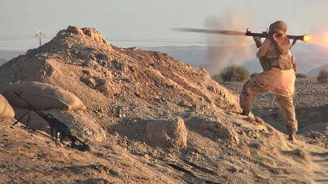 Un combatiente del Estado Islámico dispara un lanzagranadas montado en su hombro.