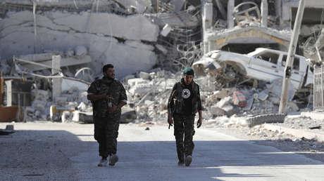 Combatientes de las Fuerzas Democráticas de Siria caminan por la línea del frente en Raqa (Siria), el 5 de octubre de 2017.