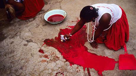 Una mujer limpia la sangre de una cabra sacrificada durante un ritual chamánico en Soweto, Suáfrica, 10 de mayo de 2005.
