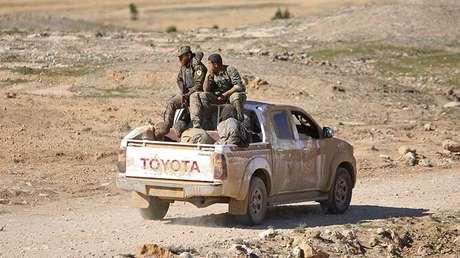 Combatientes de las Fuerzas Democráticas de Siria viajan en una camioneta con combatientes prisioneros del Estado Islámico cerca de la ciudad siria de Al Shadadi, 18 de febrero de 2016.