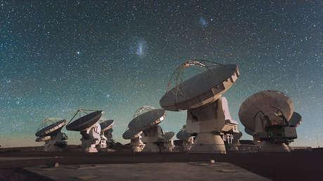 La Pequeña y la Gran Nube de Magallanes, dos galaxias cercanas a nuestra Vía Láctea, brillan en el cielo nocturno en el centro de la fotografía.