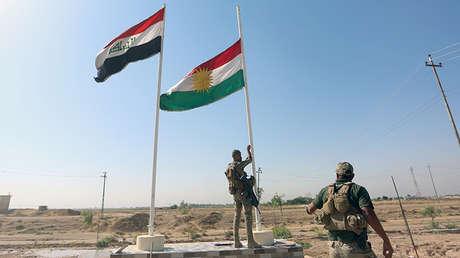 Un miembro de las fuerzas de seguridad iraquí baja una bandera kurda en Kirkuk, Irak, el 16 de Octubre de 2017.