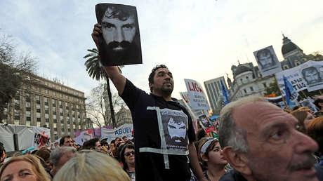Un hombre muestra una fotografía de Santiago Maldonado durante una manifestación en Buenos Aires para reclamar su búsqueda
