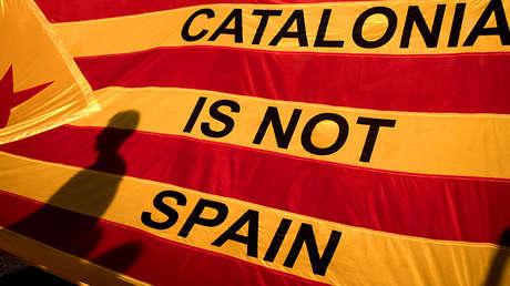 Las sombras de los manifestantes se ven reflejadas en una bandera catalana en el marco de una protesta independentista en la Plaza Universitat
