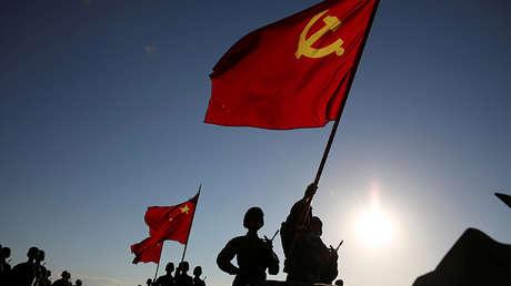 Soldados con banderas del Partido Comunista Chino y banderas nacionales en un desfile militar el 30 de julio de 2017.