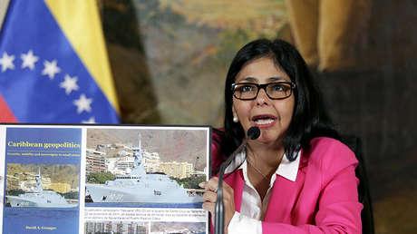 La excanciller venezolana Delcy Rodríguez muestra un cartel con fotos de un libro escrito por el presidente de Guyana, David Granger, 8 de octubre de 2015.