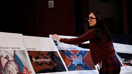 Una ayudante coloca capturas de pantalla de Facebook durante la comparecencia de representantes de Facebook, Google y y Twitter ante el Comité de Inteligencia de la cámara baja del Congreso.