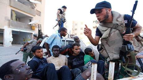 Combatientes rebeldes libios vigilan a un grupo de detenidos durante una lucha por expulsar a las fuerzas de Muamar el Gadafi en Trípoli, Libia, 25 de agosto de 2011.