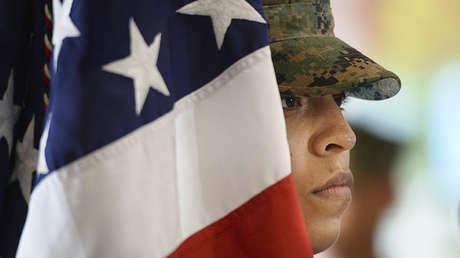 Un miembro de la Armada de EE.UU. junto a la bandera nacional.