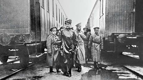 El hijo de Nicolás II, Alexéi, (izquierda), la emperatriz Alejandra Fiódorovna (segunda desde la izquierda) y el zar Nicolás II (tercero desde la izquierda) cerca de los vagones de ferrocarril