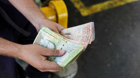 Un trabajador cuenta bolívares venezolanos en una gasolinera de la petrolera estatal venezolana PDVSA.