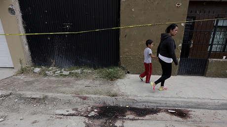 Una mujer y su hijo pasan frente a un charco de sangre ya seca y una fachada agujereada por balas en Ocotlán (México), el 20 de marzo de 2015.
