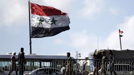 La gente camina junto a una bandera nacional siria en el puente del Presidente de Damasco.