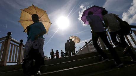 Personas se protegen del sol con sombrillas.