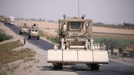 Un vehículo militar de desminado de EE.UU. encabeza un convoy en una carretera de Raqa, Siria