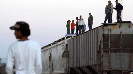 Migrantes centroamericanos parados sobre los vagones de 'La Bestia', en su viaje hacia EE.UU.