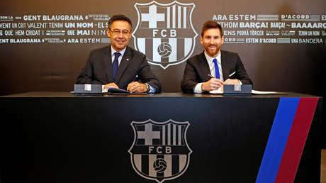 El presidente del FC Barcelona, Josep María Bartomeu, y el argentino Lionel Messi durante la firma del nuevo contrato.