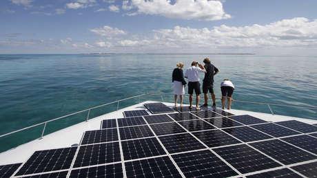 Cuatro personas observan el mar desde el bote con energía solar más grande del mundo.