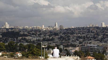 Un hombre sentado con una vista de Jerusalén de fondo en Givat HaMatos, un barrio al sur de Jerusalén.