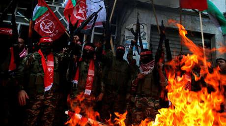 Militantes del Frente Popular para la Liberación de Palestina queman banderas de Israel y EE.UU. durante una protesta en Gaza el 7 de diciembre.