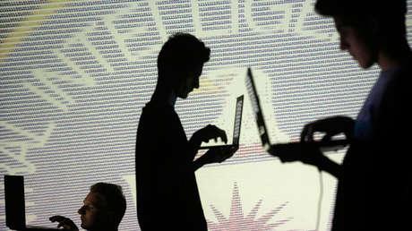 Siluetas de tres personas con computadoras portátiles frente a una pantalla con código binario y un emblema de la CIA.