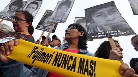 Personas con imágenes de las víctimas del conflicto guerrillero en los años 80 y 90 después de que el presidente peruano Pedro Pablo Kuczynski indultó al expresidente Alberto Fujimori en Lima, Perú, el 25 de diciembre de 2017.