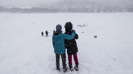 Niños jugando sobre una colina durante fuertes nevadas en Toronto, Canada.