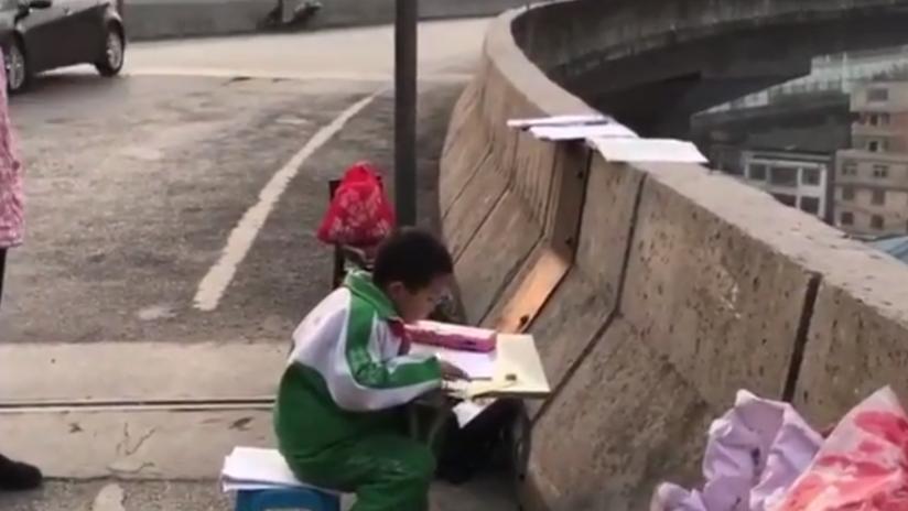 Un niño chino se ve obligado a hacer sus deberes en un paso elevado porque su casa es muy oscura