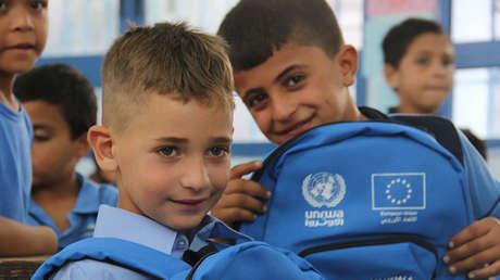 Niños palestinos lucen las mochilas con material escolar entregadas por la UNRWA.