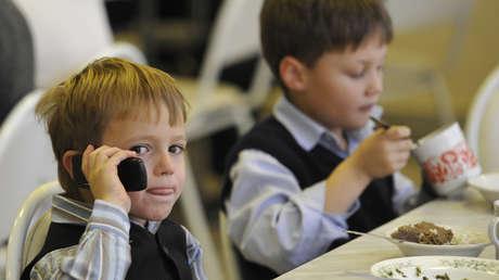 Un niño utiliza su celular durante la comida en su escuela.